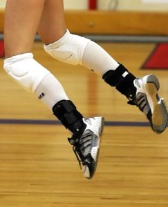 volleyball player jumping, wearing knee pads and ankle braces