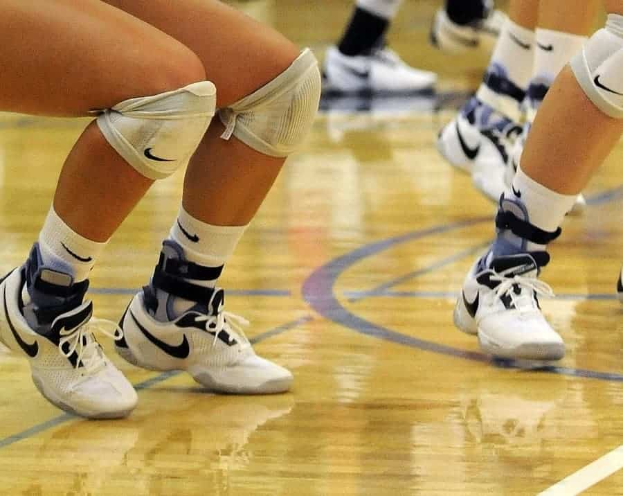 showing the legs of multiple volleyball players wearing ankle braces