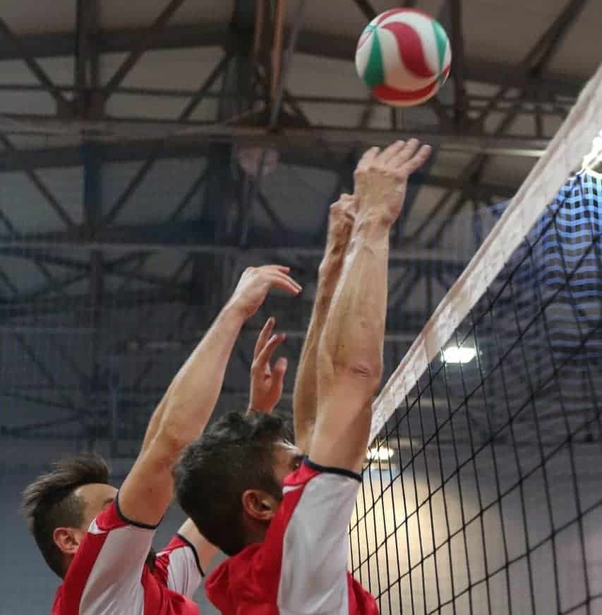 Two players blocking the volleyball