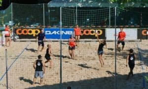 6 adults playing recreational beach volleyball