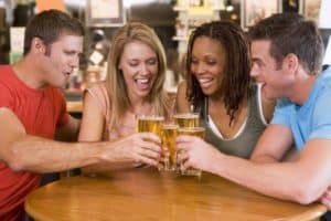2 women and 2 men toasting with beer glasses