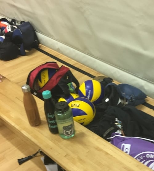bench with volleyballs, bags, and waterbottles