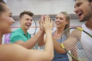 2 men and 2 women holding squash racquets doing a high five
