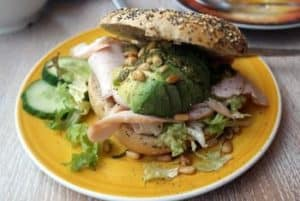 bagel with avocado and turkey on a plate