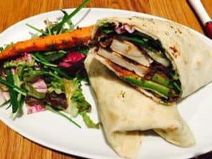chicken wrap on a plate with a side salad