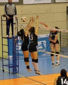 female spiking the volleyball with two blockers, with ref looking on