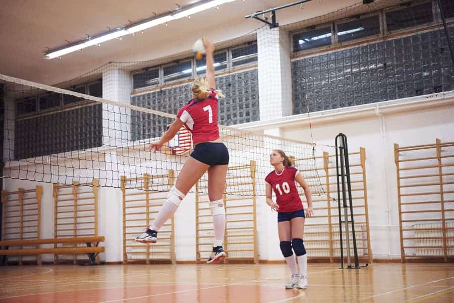 female volleyball player hitting the ball with the setter looking on