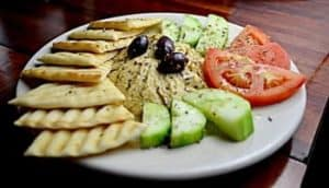 pita crackers, hummus, sliced tomatoes and sliced cucumbers on a plate