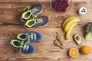 running shoes with fruits on a wooden table