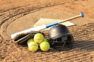 a softball bat leaning on a helmet and a pile of 4 softballs, with home plate in the background