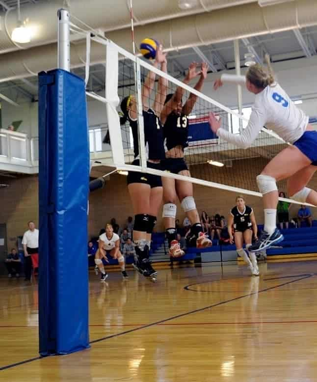 female volleyball player hitting the ball with two blockers across the net
