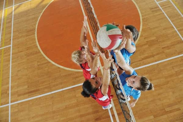female volleyball player hitting against a block