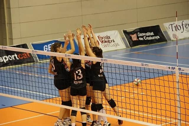group of female volleyball players giving high fives with hands up