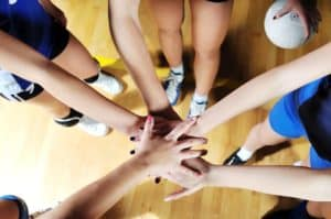 volleyball team huddle, hands in the middle