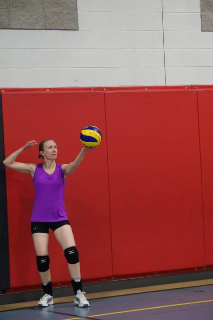 female volleyball player serving the volleyball