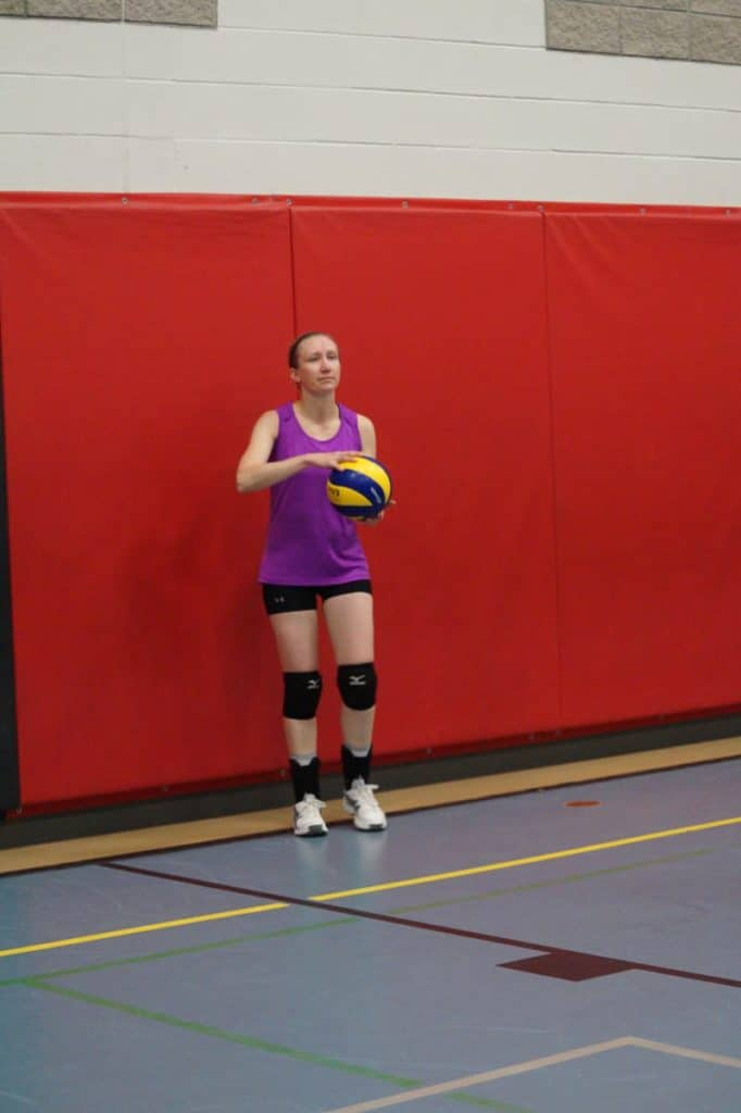 female getting ready to serve a volleyball