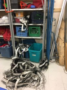 volleyball net tangled up on floor of sports equipment room