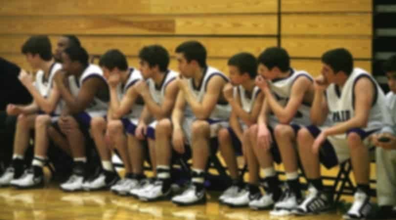 male basketball players sitting on a bench, focused on the game