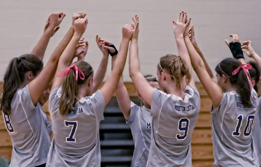 women's volleyball team doing a group high 5 during a huddle