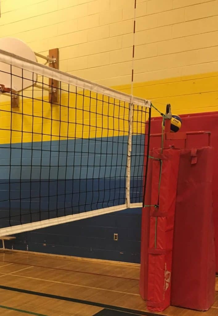 volleyball net and ref stand with volleyball perched on top