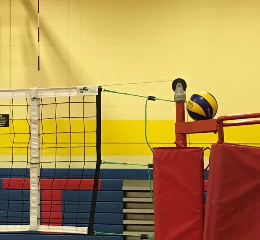 volleyball ref stand with volleyball perched on top and part of net showing
