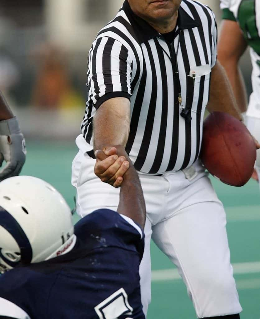 football referee helping up a player
