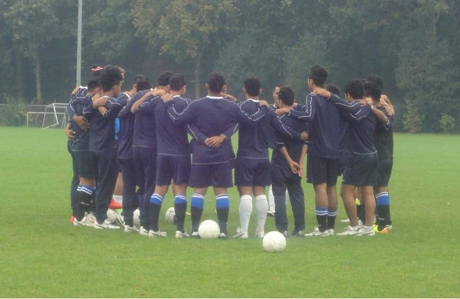 male soccer team in a huddle
