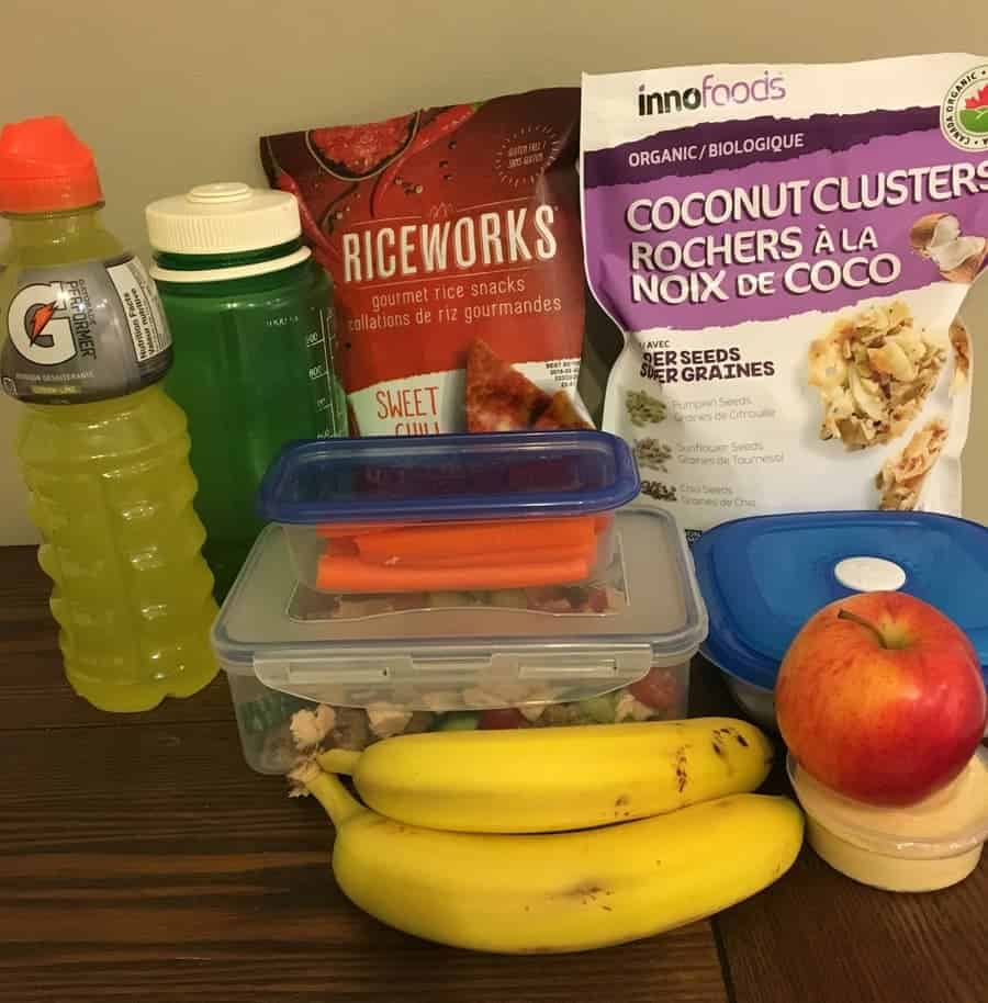 healthy lunch, including bananas, apple, carrot sticks, gatorage, water bottle, rice crackers, and coconut chips
