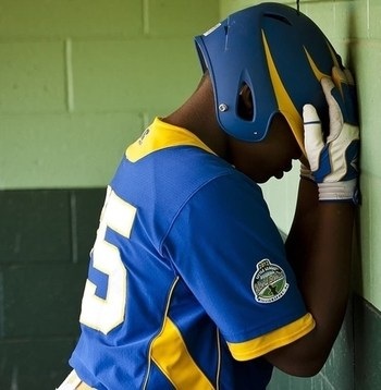unhappy baseball player leaning against a wall