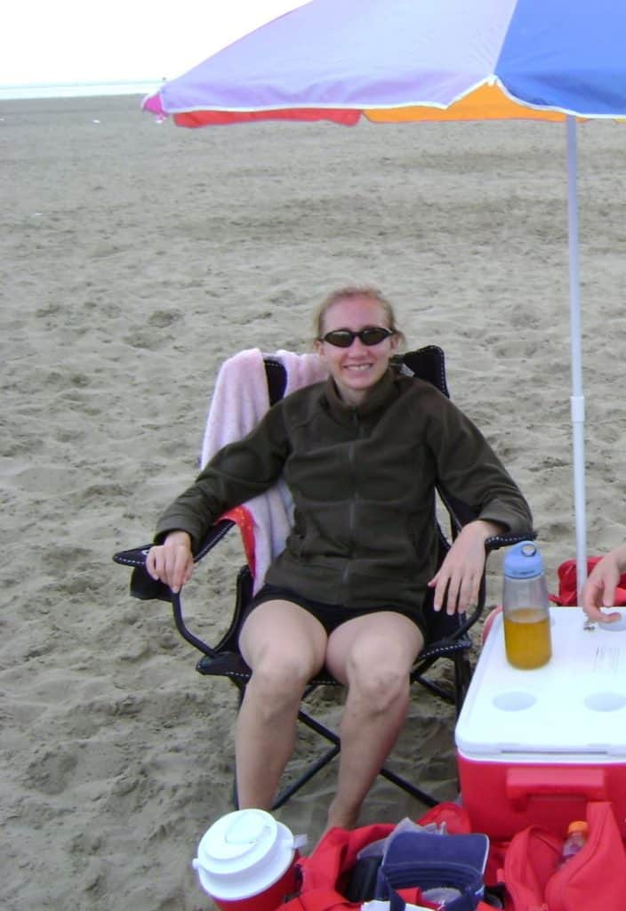 woman sitting on beach in chair under an umbrella and wearing sunglasses