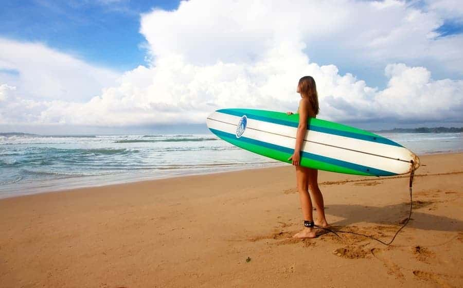 woman standing on beach holding a surfboard watching the waves