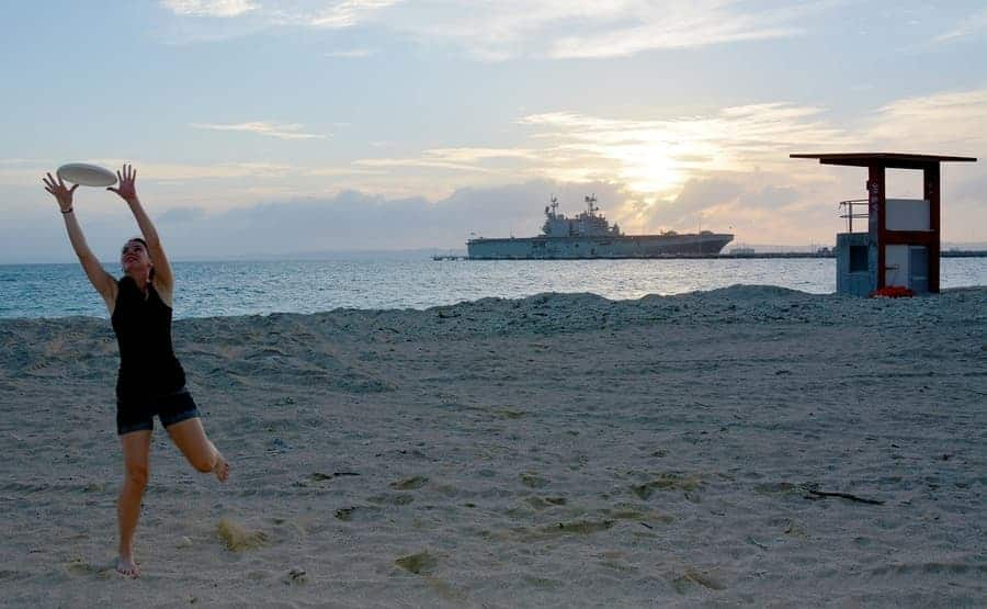 girl playing frisbee on beach with ocean liner in the background