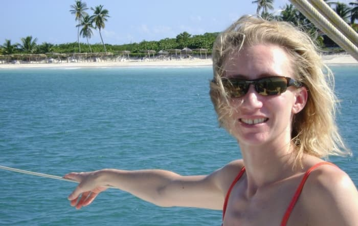 blonde woman wearing sunglasses with beach shoreline in the background