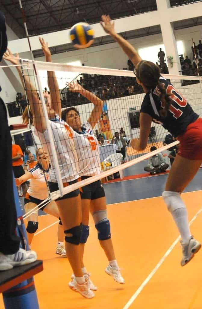 woman spiking a volleyball against 2 blockers