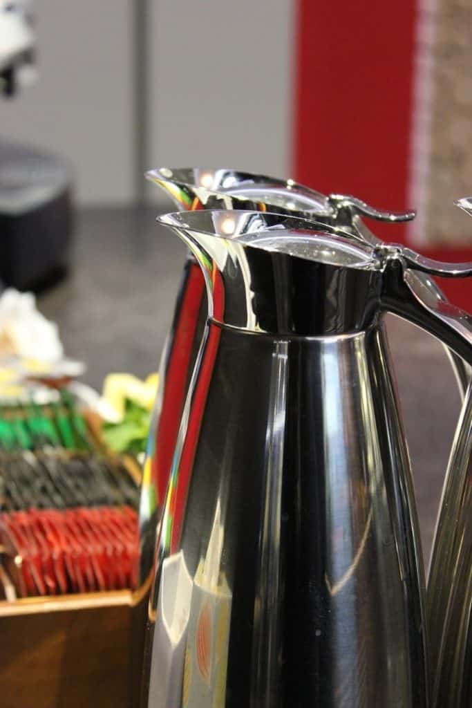 two stainless steel jugs on a buffet table