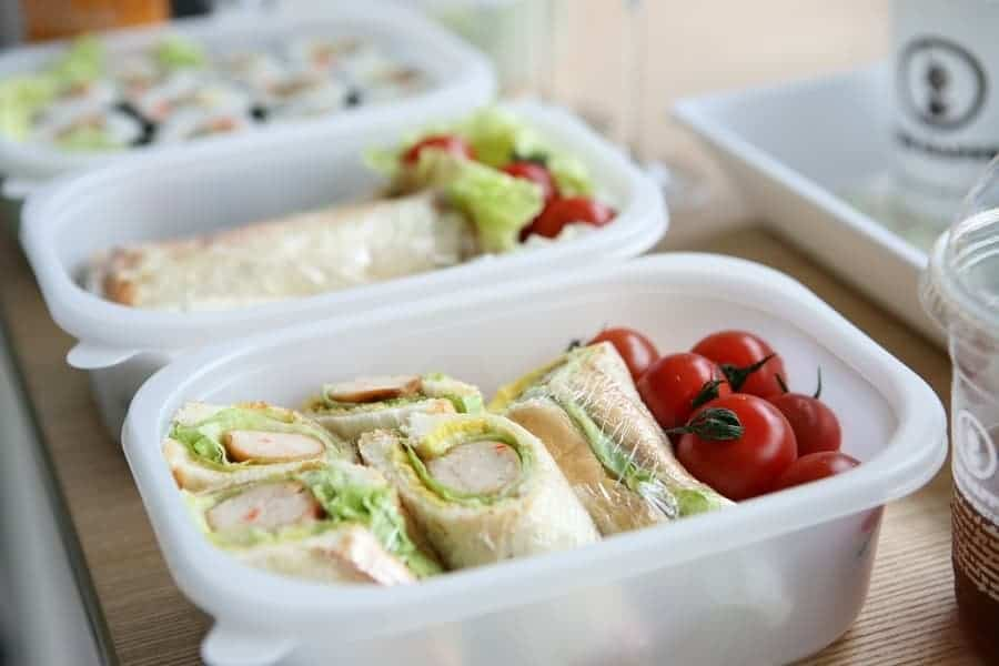 variety of sandwiches and wraps in different plastic containers