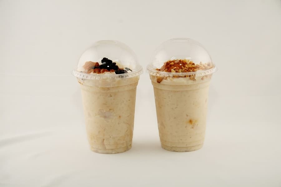 two plastic containers with yogurt, granola, and fruit