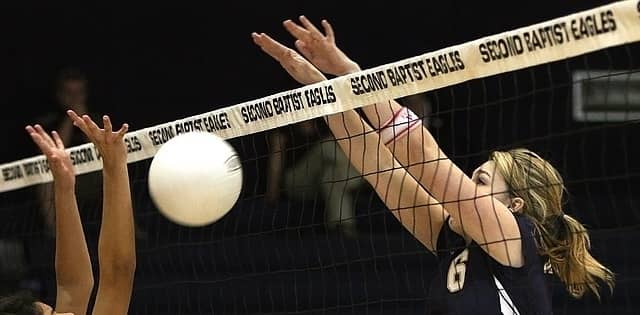 Woman blocking a volleyball at the net